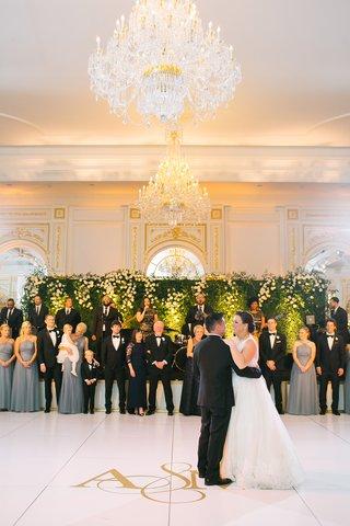 bride-in-sleeveless-wedding-dress-with-groom-dance-floor-first-dance-gold-monogram-white-floor-band