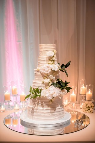 wedding reception white buttercream frosting wedding cake no cake topper but fresh white rose and leaf