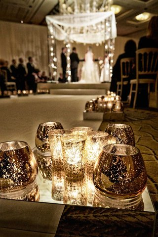 small-candle-votives-on-mirrors-stand-at-jewish-and-christian-interfaith-ceremony
