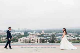 wedding photo of bride and groom walking toward each other during first look rooftop beverly hills