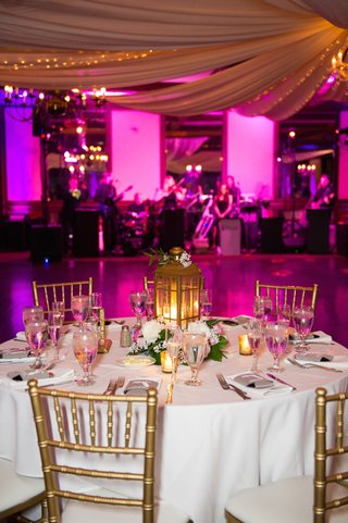 round-table-with-gold-chairs-and-lantern-next-to-dance-floor