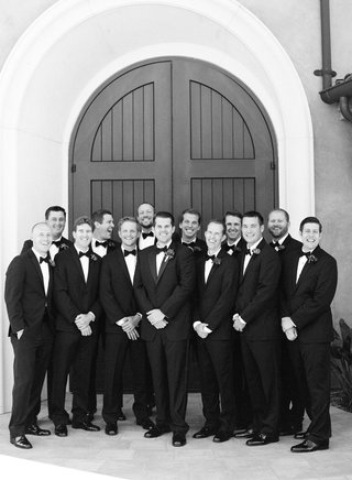 black-and-white-photo-of-groom-with-12-groomsmen-in-tuxedos-and-bow-ties