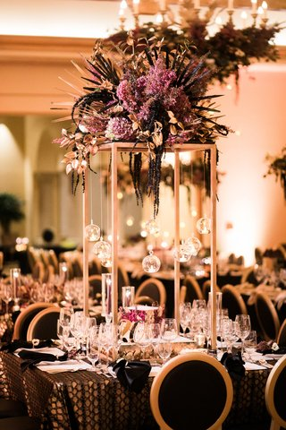 rectangular-structure-with-purple-flowers-and-palm-fronds-on-top-unique-centerpieces