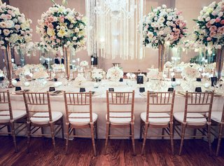 long-wedding-reception-table-with-gold-chairs-high-and-low-centerpieces-greenery-orchid-rose-flowers
