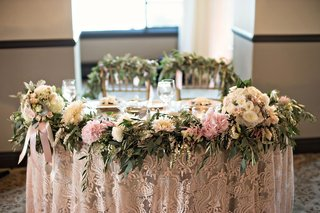 sweetheart-table-patterned-linens-floral-garland-in-front-greenery-of-backs-of-chiavari-chairs