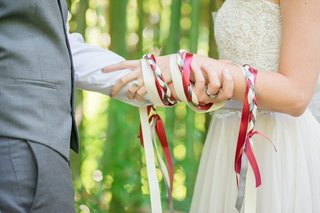 hand-fasting-ribbon-chord-silk-red-white-gray-tied-around-hands-celtic-wedding-tradition-ceremony
