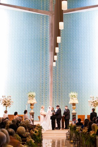 bride-and-groom-at-altar-with-tall-flower-arrangements