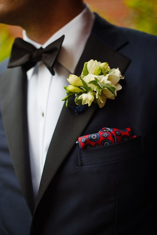 groom-in-tuxedo-bow-tie-white-cluster-boutonniere-and-red-blue-pocket-square