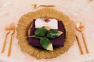 wedding-reception-place-setting-gold-charger-plate-purple-napkin-green-leaves-place-card-flatware