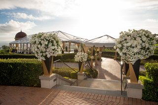 wedding-ceremony-resort-at-pelican-hill-ceremony-space-rotunda-flowers-at-stair-entrance-pathway