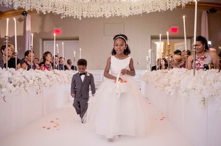 wedding-ceremony-white-flowers-on-side-of-aisle-flower-girl-tossing-pink-petals-white-basket