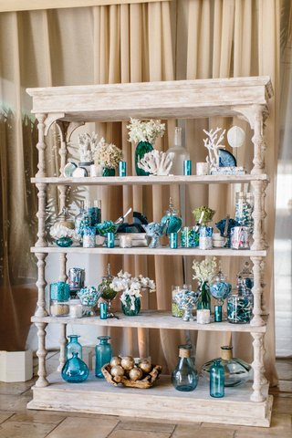 white-wash-wood-book-shelf-with-coral-blue-vases-couples-favorite-candy-and-desserts-agate-slices