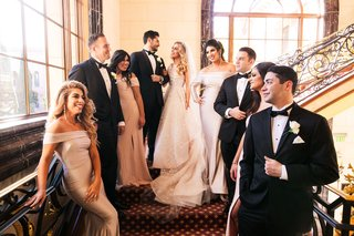 bride-and-groom-on-stairs-with-bridesmaids-in-off-shoulder-gowns-and-groomsmen-in-tuxedos-white