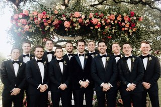 groom-with-groomsmen-in-tuxedos-bow-ties-groom-with-feather-bow-tie-pink-greenery-chuppah
