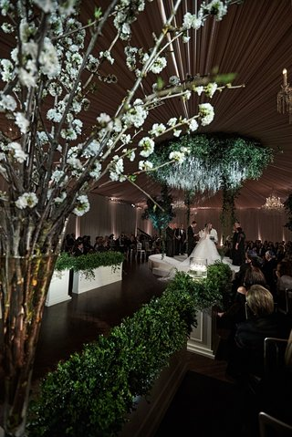 wedding-ceremony-decor-ballroom-cherry-blossom-branches-green-hedges-circle-chuppah-jewish-ceremony