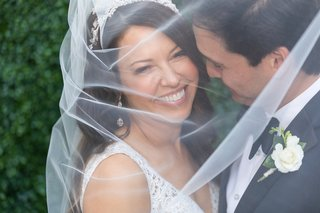 bride-and-groom-smiling-with-veil-draped-over-their-faces