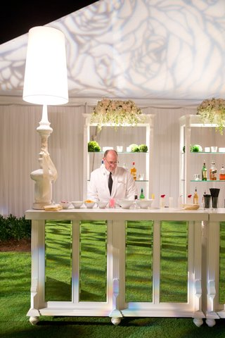 bartender-in-white-suit-at-white-and-mirror-buffet-table
