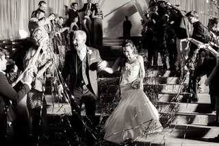 bride-and-groom-exiting-reception-streamers-guests-black-and-white-trumpet-gown-tuxedo-smiles