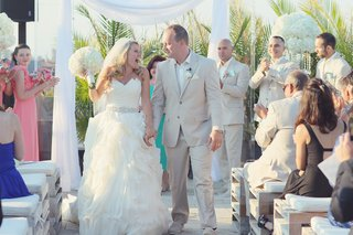 bride-in-maggie-sottero-gown-with-groom-in-tan-suit-leave-ceremony
