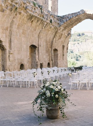 outdoor-wedding-reception-in-old-building-ruins-italy-countryside-white-chairs-white-flowers-verdure