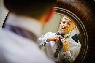 scott-blokker-putting-on-purple-tie-in-mirror