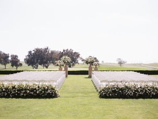 wedding-ceremony-grass-lawn-golf-course-wedding-hotel-venue-white-chairs-greenery-flowers-simple
