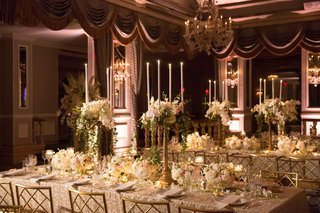 long-tables-with-white-linens-and-small-floral-arrangements-with-tall-candelabra-foliage-flowers