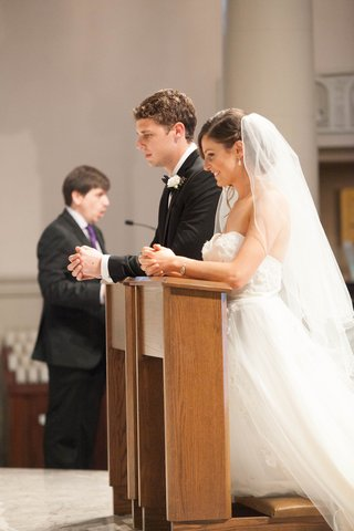 bride-in-winnie-couture-wedding-dress-and-groom-in-prayer-at-catholic-ceremony