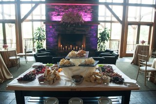wood-table-topped-with-fresh-grapes-cheeses-and-breads