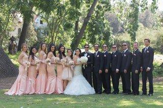 bride-in-mermaid-wedding-dress-with-groom-in-tux-sunglasses-pink-bridesmaid-dresses-groomsmen-suit