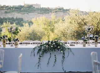 wedding-reception-outdoor-italy-destination-white-head-table-greenery-cascading-vines-umbria-candles
