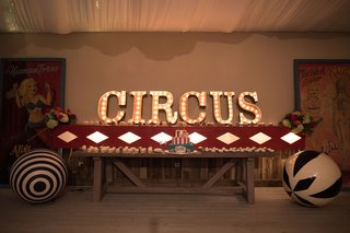 dessert-table-with-circus-theme-cake-and-cupcakes-with-circus-marquee-lettering-and-big-balls