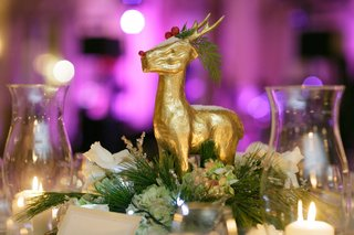 holiday-wedding-reception-table-with-a-gilded-reindeer-evergreen-green-hydrangeas-white-roses