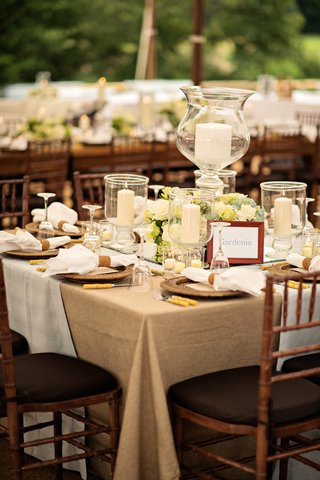tented-wedding-reception-with-table-covered-in-tan-tablecloth-and-white-fabric-candles