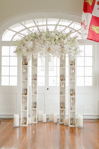 wedding-altar-with-suspended-white-orchids-roses-pink-roses-curly-willow-over-narrow-bookcases