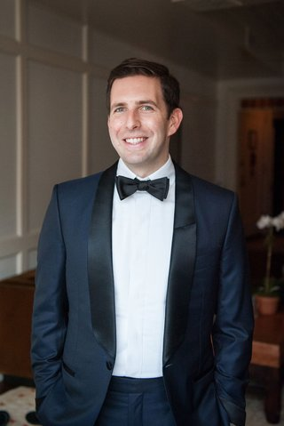 wedding-attire-for-groom-navy-blue-tuxedo-jacket-with-black-lapels-and-bow-tie
