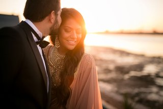 bride-and-groom-at-sunset-in-lehnga-and-tuxedo-for-dinner-with-friends-and-family