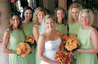 bride-with-bridesmaids-in-green-gowns-and-holding-orange-flowers
