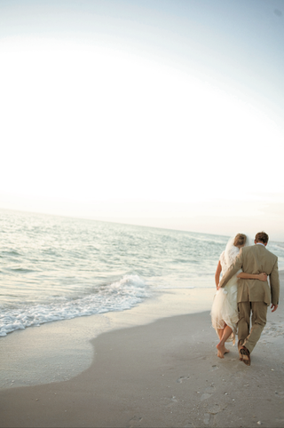 bride-and-groom-walking-barefoot-on-beach-at-sunset