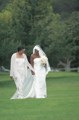 bride-holds-moms-hand-while-walking-on-grassy-resort-grounds