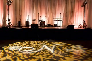 wedding-reception-with-a-gold-damask-and-monogram-projection-on-the-dance-floor
