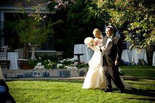 father-escorting-bride-down-grassy-aisle