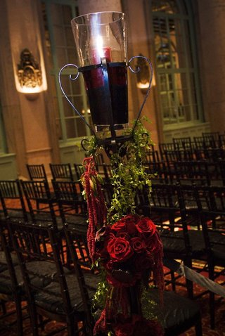 wrought-iron-stand-decorated-with-greenery-and-red-roses-topped-with-red-pillar-candle