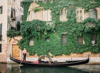 venice-italy-wedding-gondola-decorated-with-greenery-and-flowers-man-in-red-and-white-stripe-shirt