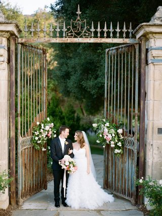 bride-in-strapless-monique-lhuillier-wedding-dress-in-front-of-iron-gates-at-wedding-venue-flowers