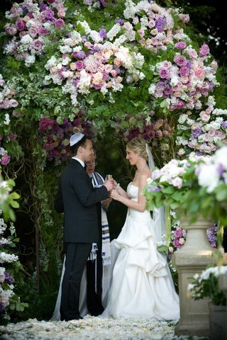 rabbi-performing-wedding-under-floral-chuppah
