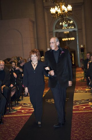 lady-in-a-black-pant-suit-is-escorted-down-the-aisle-by-a-gentleman-in-a-black-velvet-blazer