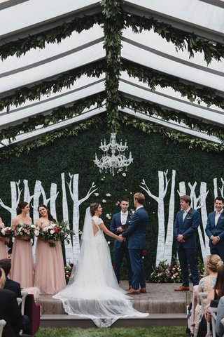 wedding-ceremony-decor-clear-top-tent-greenery-chandelier-hedge-wall-birch-tree-design-bridesmaids