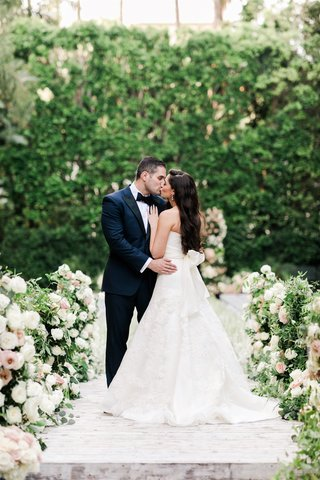 bride in vera wang wedding dress with bow in back kissing groom in tuxedo at four seasons ceremony
