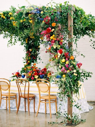 A Charming Fete Colorful Reception flowers hanging from arbor over table